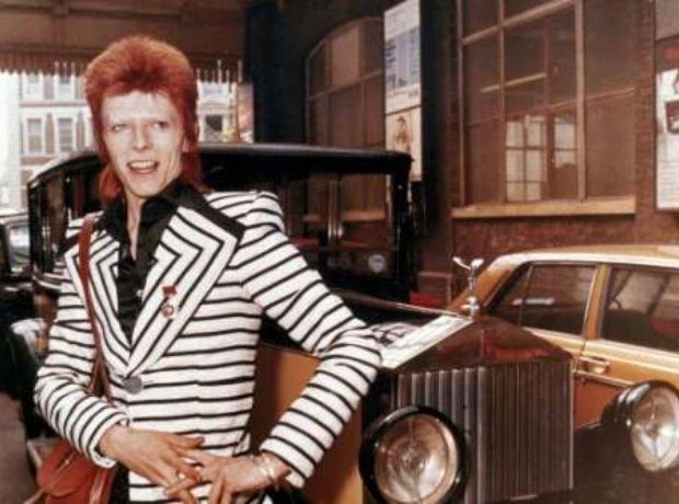 British rock singer, David Bowie, poses beside his