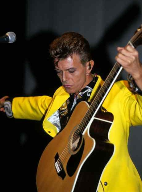 Bowie in yellow jacket, playing guitar